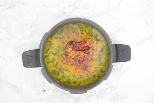 Tempering poured over the cooked palak dal.