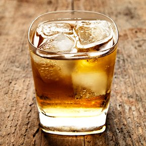 a glass of scotch and soda with ice