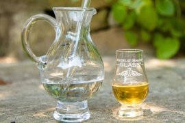a small water carafe adjacent to a half full glass of whisky