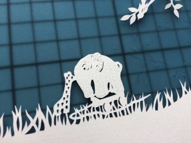 Papercut Birth Announcement - Aksel - detail toys on mat - Whispering Paper