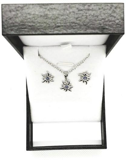 Ensemble pendentif et boucles d'oreilles Edelweiss en argent 925. Livré dans un écrin avec une chaîne. Avec différentes couleurs modèle by White Alpina. Zircon bleu