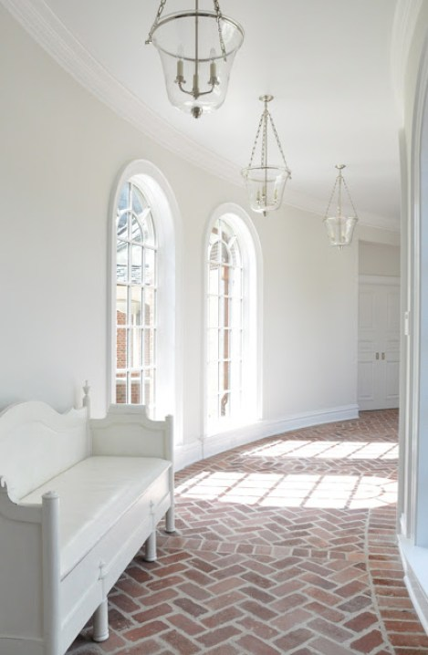 kathleen clements curved hallway hall arched windows brick floors herringbone pattern lanterns white walls cococozy