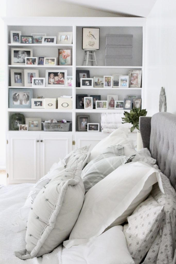 White Cottage Master Bedroom- gray- white- green- shabby chic bedroom- farmhouse decor- layered mirrors- painted gray furniture- DecoArt- Repose Gray- white bedding- white painted furniture- Armoire- fireplace in the bedroom- home design- large bedroom space- sitting area in the bedroom- bookshelves in a bedroom- upholstered bed