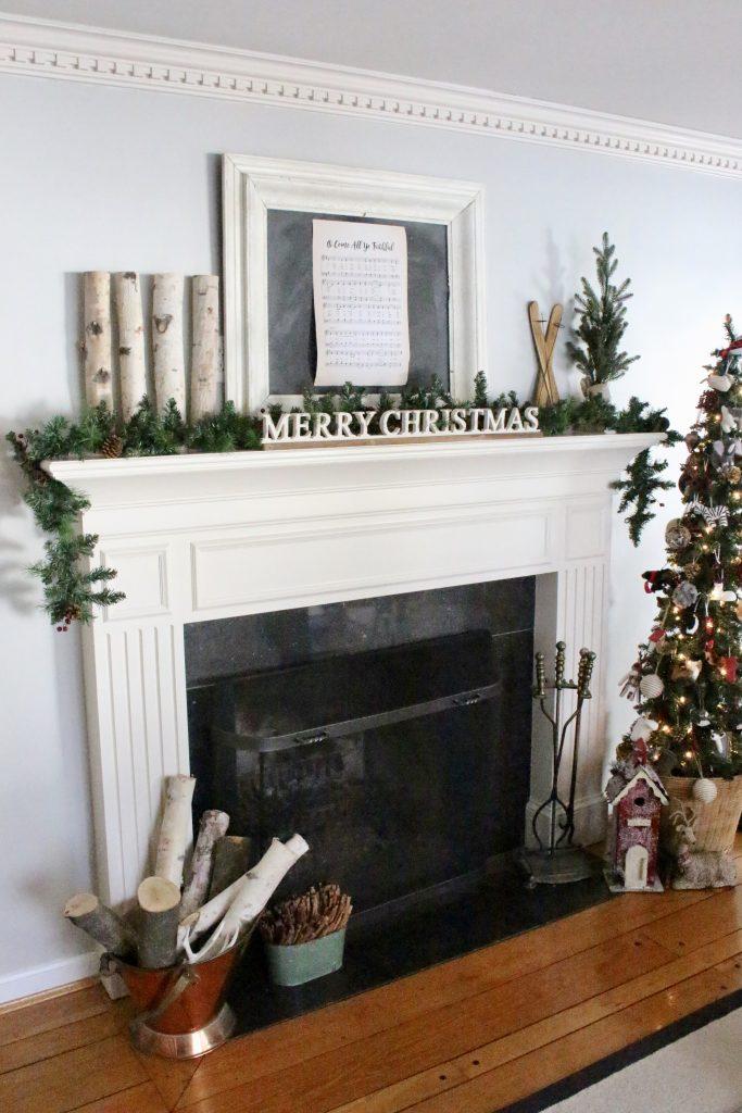 farmhouse rustic Christmas mantel- birch logs- chalkboard- animal ornaments- wicker basket- slim tree- song sheet- mantels- mantles