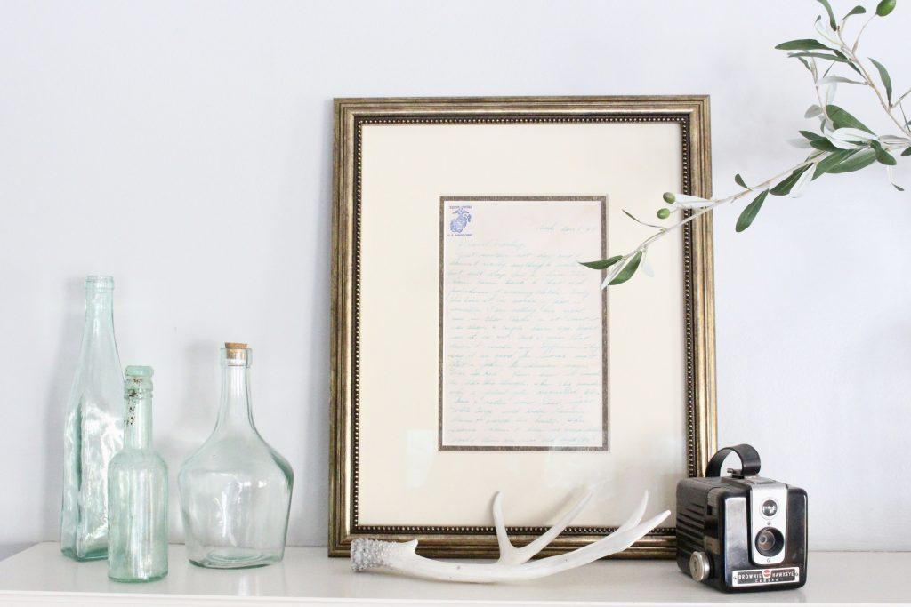 spring mantel-bottles- insulators- vintage cameras- mantel decor- decorating a mantel for spring- mantles- keepsakes- how to use keepsakes in decor- framed letters