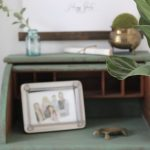 green desk- vignette- spring decor- filling a nook- fiddle fig leaf tree- brass animals- green painted furniture- vintage bottles- hanging wall canvas