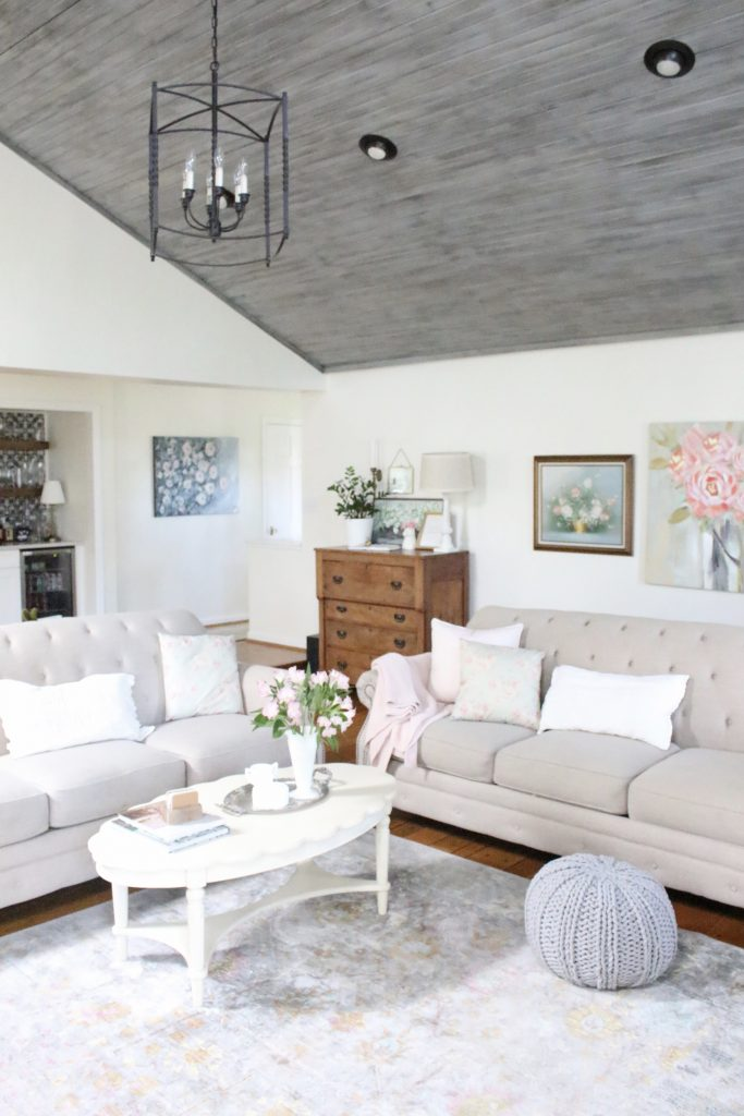 An updated family room space with seasonal spring decor, spring- family room decor- gray washed ceiling- pink decor- gray decor- using pastels in decorating- large family room space- gray ceiling