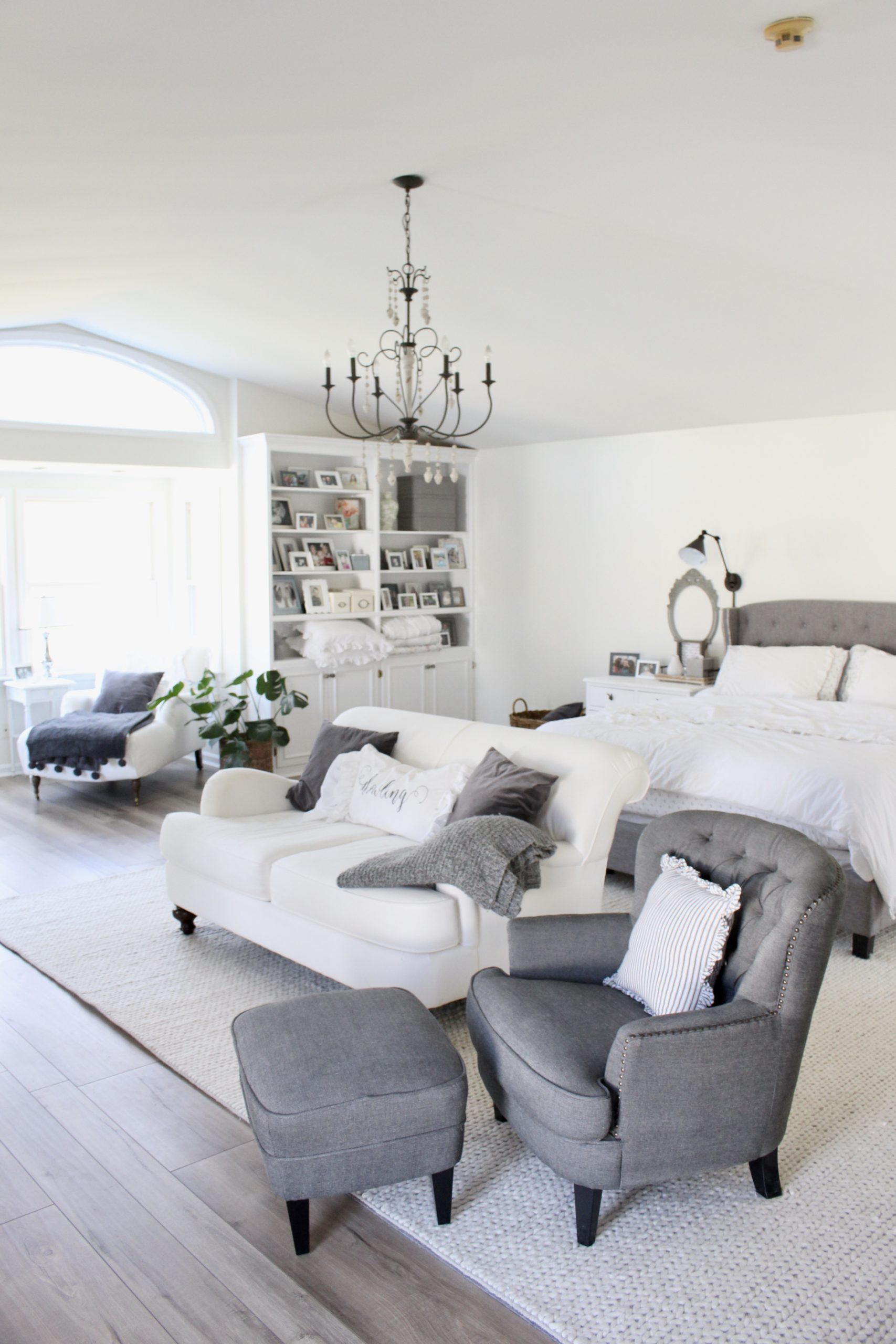 Cozy white master bedroom- An updated space with new flooring and a retiled fireplace