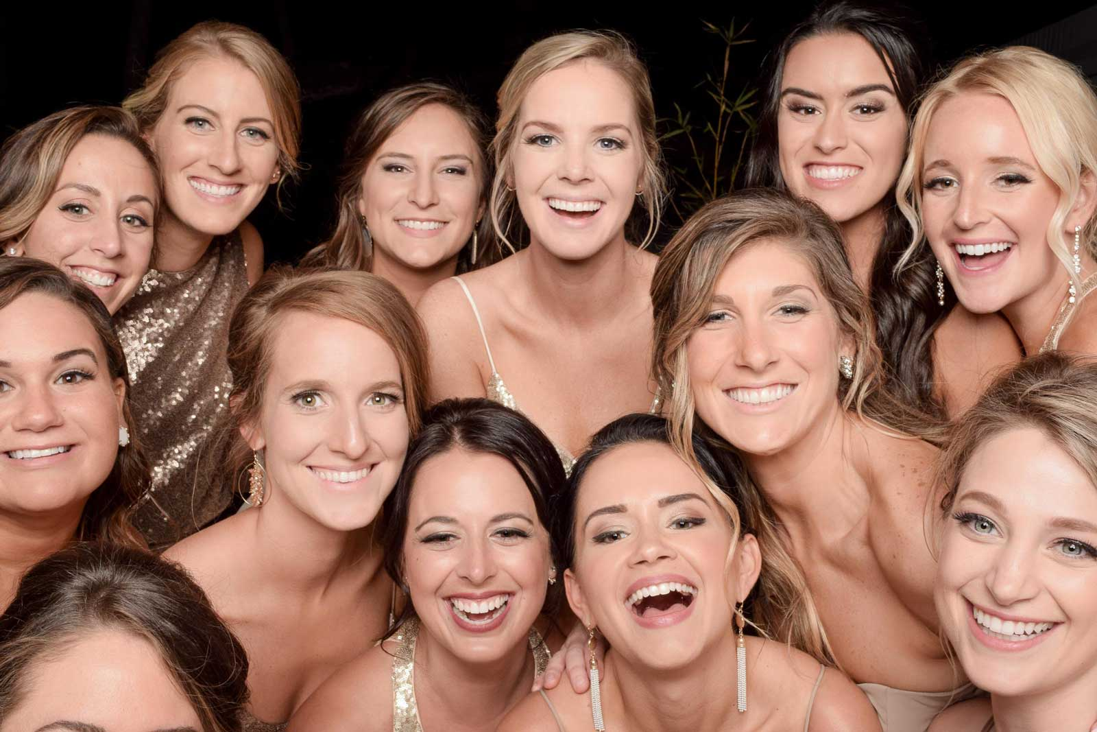 group of bridemaids smiling at the photo booth taking pictures