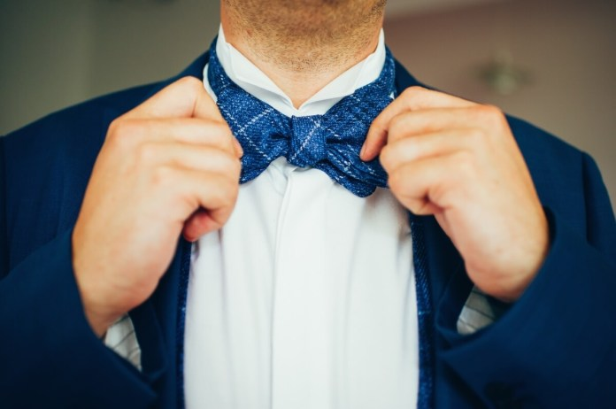 A man in a blue suit with a blue bow tie