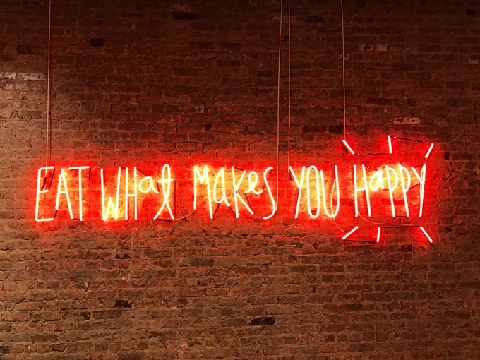 Eat What Makes You Happy on a brick wall