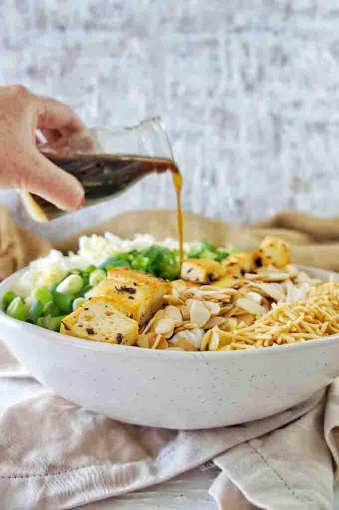 Pouring the dressing into Crispy Tofu Noodle Salad