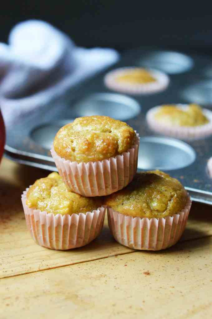 stack of mini muffins with muffin tray and an apple in the background