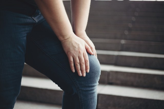 Overweight woman with knee pain climbing stairs