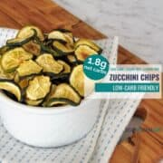 Toasted zucchini slices in a white bowl on a blue and white tea towel