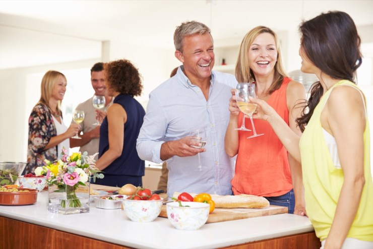Older guests greeted by friends at a dinner party