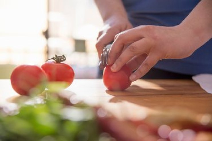Woman's hands cutting tomato at the kitchen counter