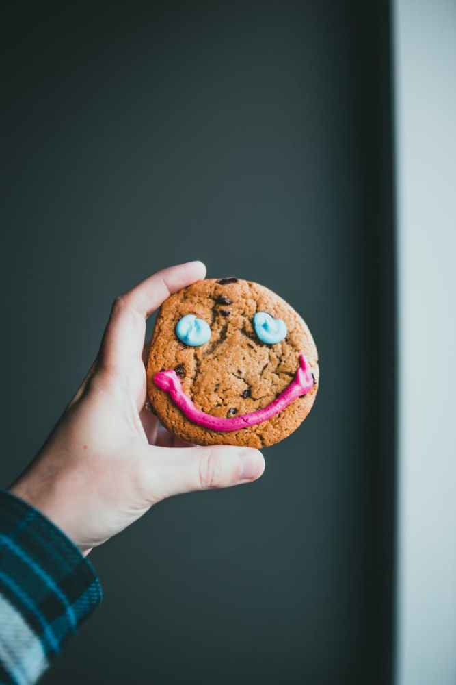 hand holding a biscuit with a smiley face in icing