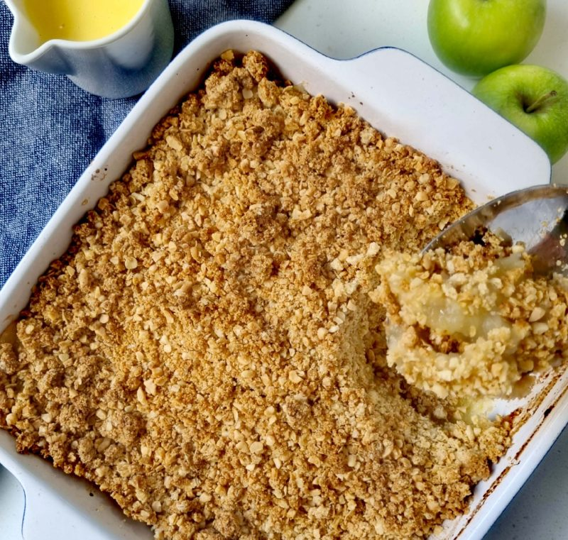Apple crumble with oats being served on a serving spoon
