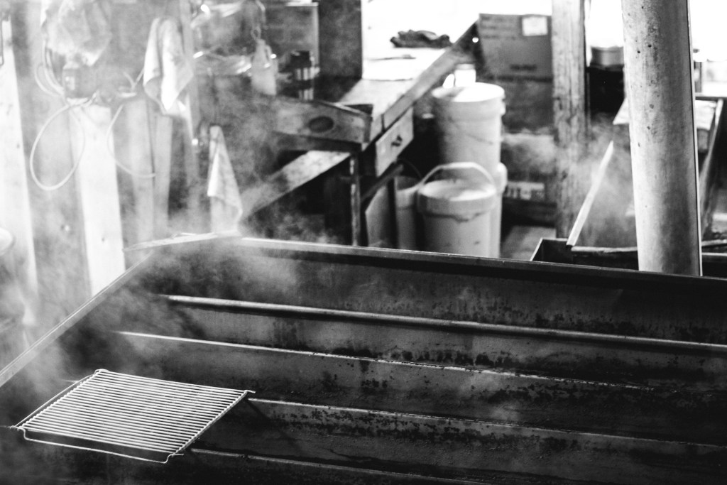 sap being boiled down into maple syrup inside a sugar house in NH | wholesomefamilykitchen.com