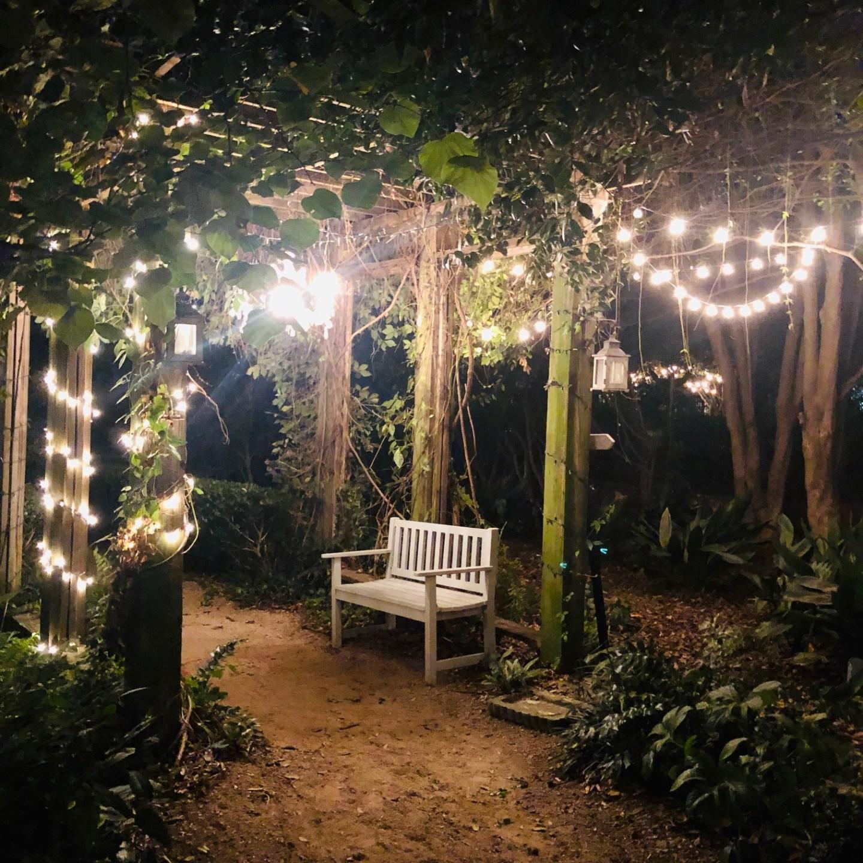 Rosie's Wine Garden in Noda, Charlotte, NC features quaint garden benches and fairy lights