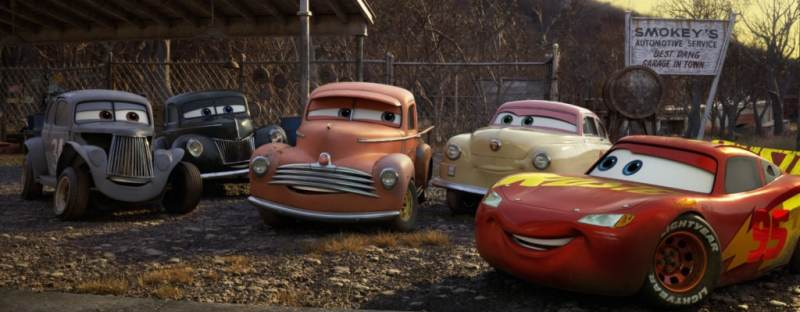 "MEET THE LEGENDS — Lightning McQueen comes hood to hood with a group of characters who represent the roots of stock car racing—and provide a link to Lightning's late coach and mentor, Doc Hudson. From left: River Scott (voice of Isiah Whitlock Jr.), Junior ""Midnight"" Moon (voice of Robert Glenn ""Junior"" Johnson), Smokey (voice of Chris Cooper), Louise ""Barnstormer"" Nash (voice of Margo Martindale), and Lightning himself (voice of Owen Wilson). ""Cars 3"" opens in U.S. theaters  on June 16, 2017. ©2017 Disney•Pixar. All Rights Reserved."