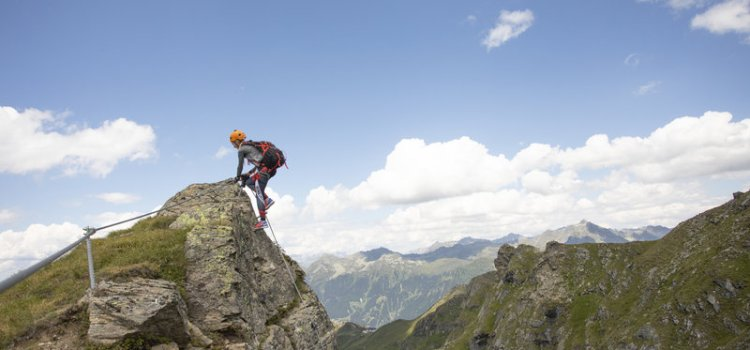 Das Bild zeigt eine Szene zum Thema Klettern Montafon. Ein MAnn seigt an einem Klettersteig auf einen Felsgrat, dahinter alpine Landschaft und Himmel mit Wolken.