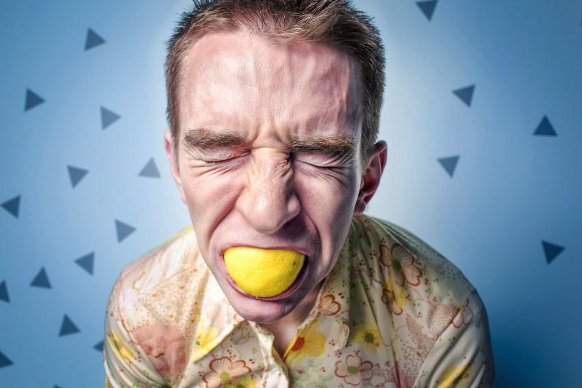 Mann beißt in Zitrone
