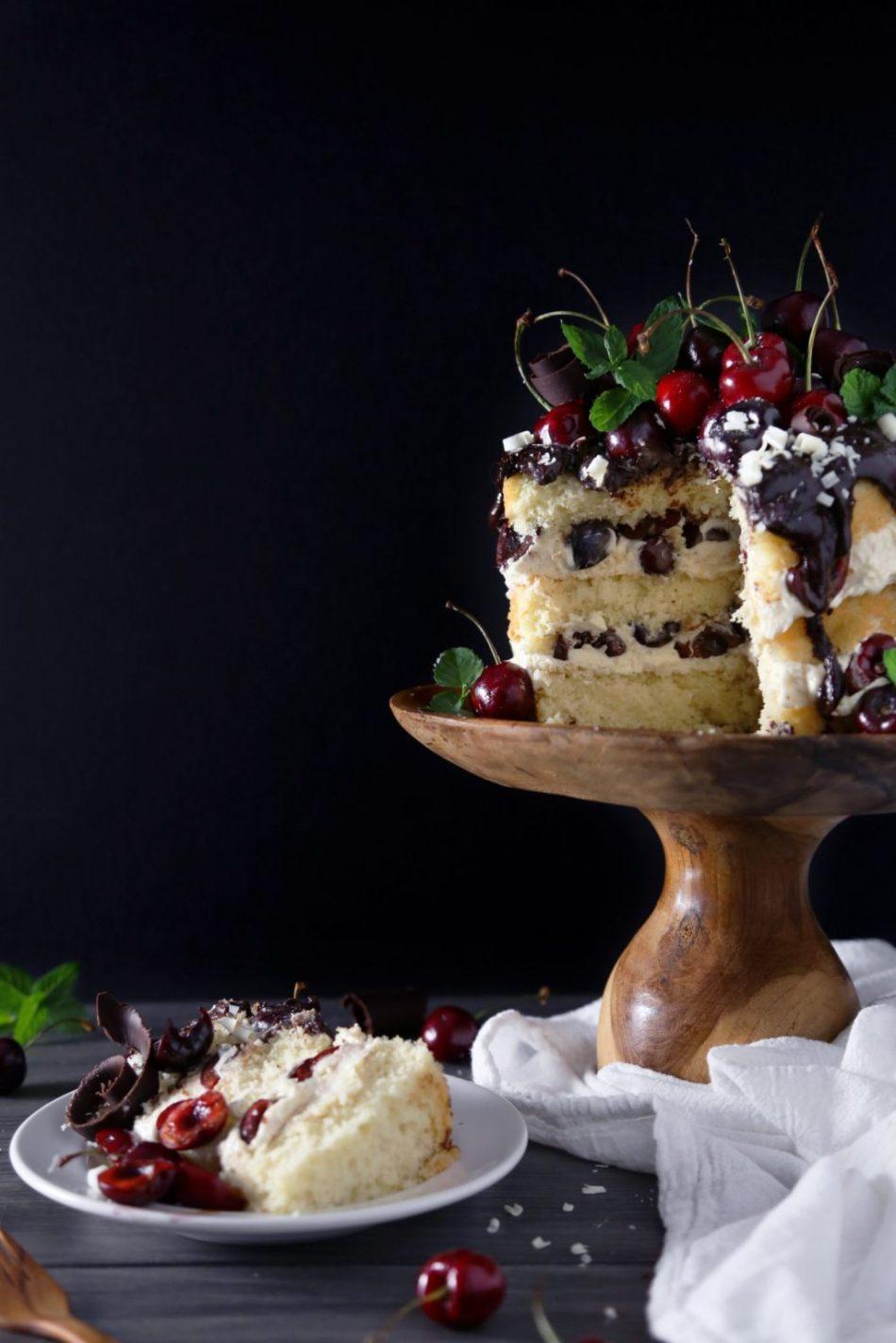 White Forest Cake | Gluten, dairy, and refined sugar free vanilla cake is topped with white chocolate buttercream, cherries, and dark chocolate ganache.