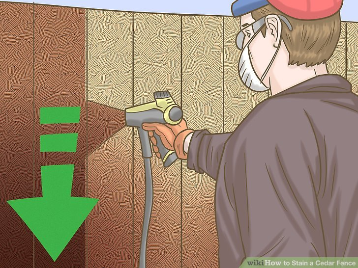 Stain the cedar fence with a spraying machine.