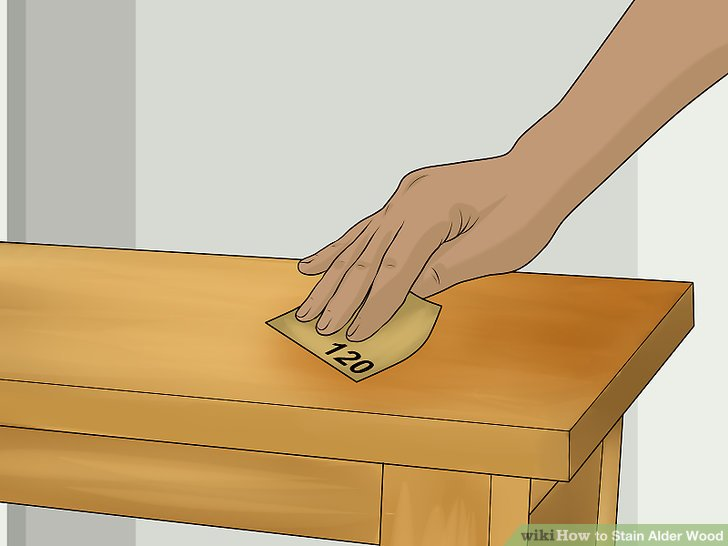 Use a medium-grit sandpaper, around 120 grit, on the entire piece of wood.