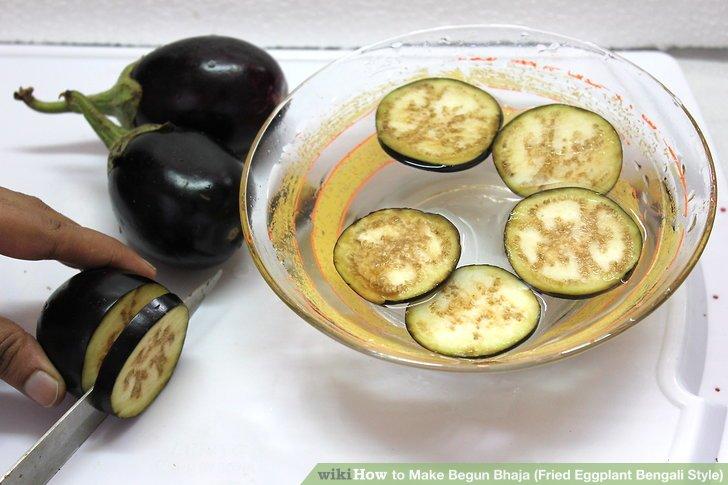 Schneiden Sie die Aubergine in ca. 1/2-Zoll-Scheiben und lassen Sie sie etwa 15 Minuten in eine Schüssel mit Wasser fallen.
