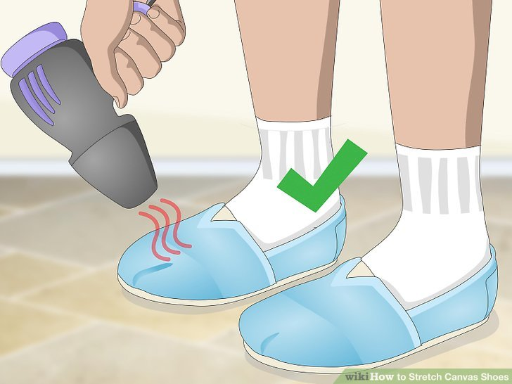 Use a hair dryer on the shoes while wearing socks.