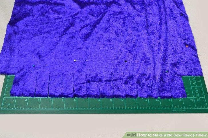 Schneiden Sie 1 Zoll (2,54 cm) breite, 2 Zoll (5,08 cm) tiefe Schlitze entlang aller vier Seiten Ihres Vlieses.