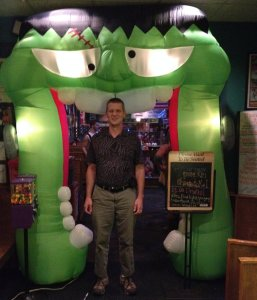 Wil stands in a blow-up green mouth with sharp teeth that is taller than he on Halloween of 2013..