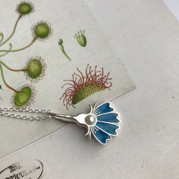 Art nouveau enamel flower necklace with pearl. Handmade in Norway. The floral pendant is made from silver and enamel. The botanical garden necklace comes with a small fresh water pearl.