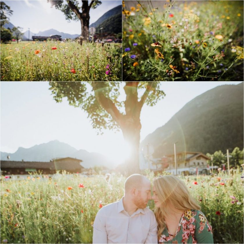 Couple sitting in front of field of wildflowers with sunset behind