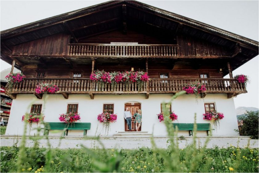 Wide shot of old Austrian farm house with couple in the door frame