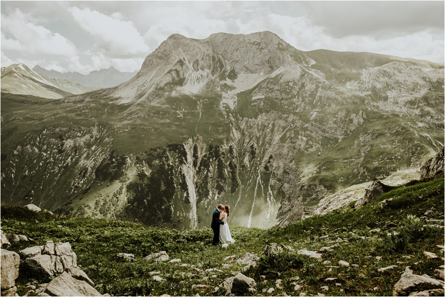 The bride and groom embrace against a mountain panorama backdrop Image by Wild Connections Photography