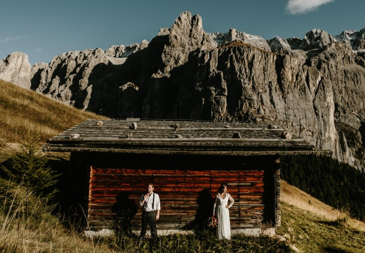 Planning a wedding in the alps - image of a bride and groom in front of a wooden mountain hut in the Italian Alps by Wild Connections Photography