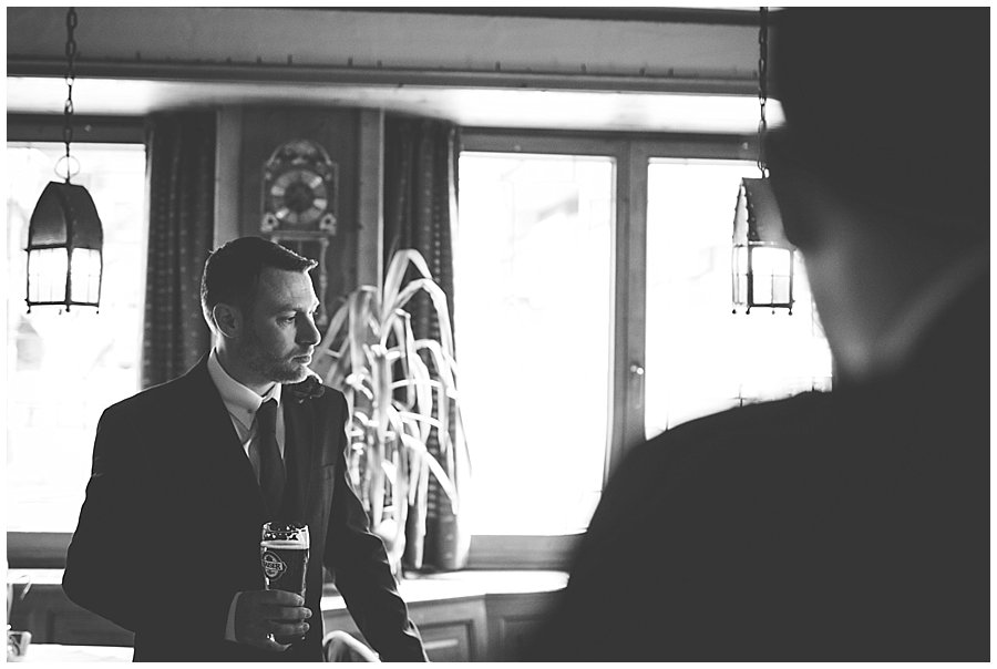 The groom Wayne drinking a beer in the hotel bar before the wedding