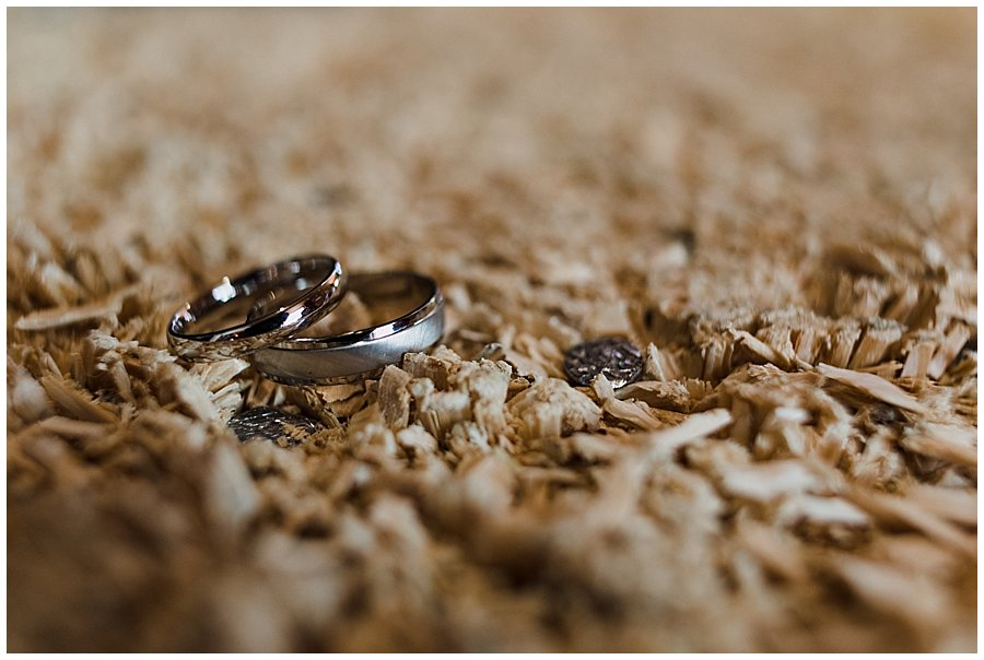The wedding rings sit on a old wooden log used for a traditional Austrian nail and hammer game