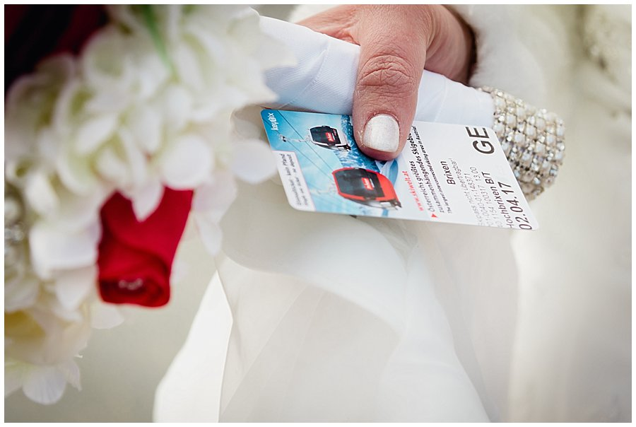 A close up of the bride Michelle holding her bouquet and a ticket for the ski lift in Brixen