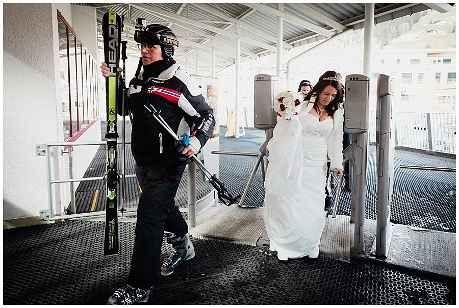 The bride enters the ski lift area along with a skier