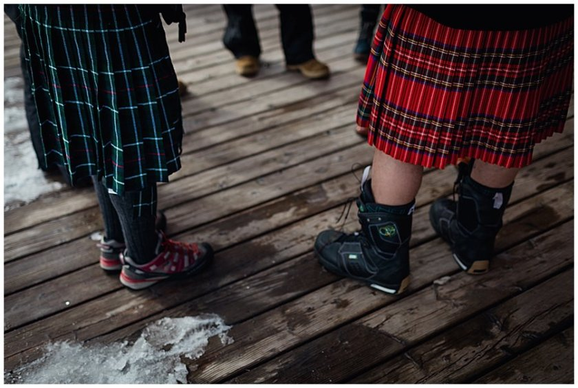 Two wedding guests wearing kilts, and one wearing snowboard boots