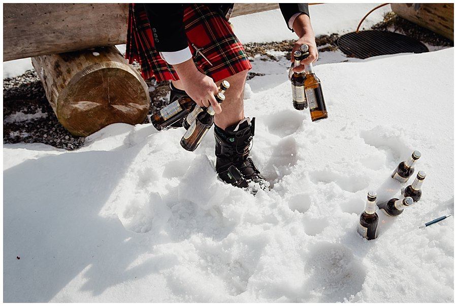 A guests collects some bottles of beer which were being kept cool in the snow