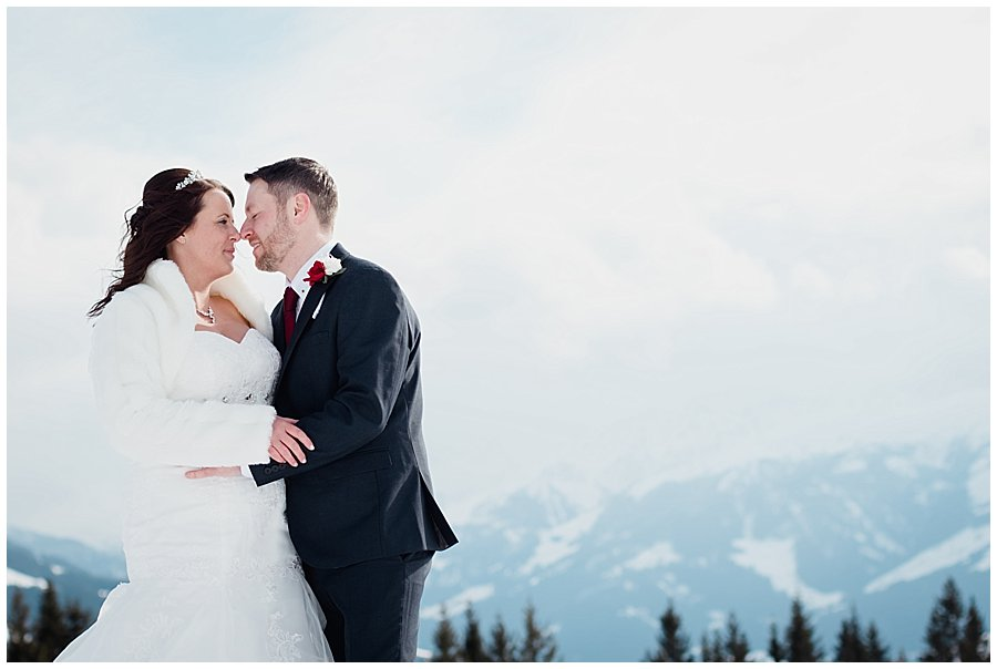 Wayne and Michelle embrace whilst standing on the top of the mountain with snow covered mountains behind them in the distance