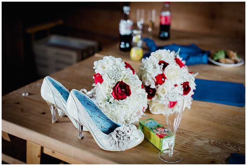 The bride's shoes and bouquet lie on a wooden table with an empty champagne glass and juice carton.