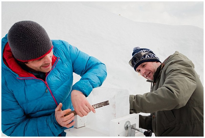Two male wedding guests with chisels begin carving their block of ice