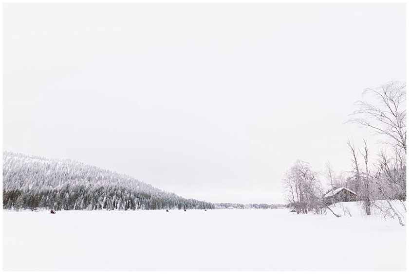 Skidoos drive across a Frozen Lake in Levi Finland by Wild Connections Photography